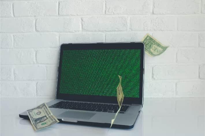 Hacked laptop with american dollar bills falling